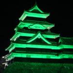 世界緑内障週間にあわせて緑色にライトアップされた松本城